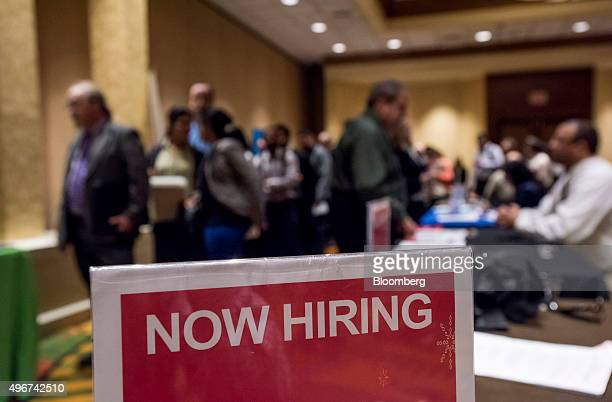 'Now Hiring' signage is displayed as job seekers wait in line to enter the San Jose Career Fair in San Jose California US on Tuesday Nov 10 2015 The...