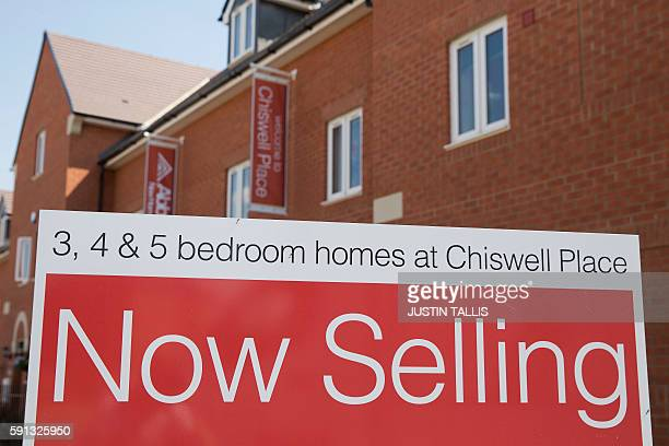 A Now Selling sign is pictured outside homes for sale on a newly built housing estate in New Cardington near Bedford north of London on August 17...