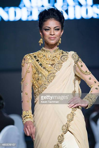Noyonika Chatterjee walks on stage during the inaugural amfAR India event at the Taj Mahal Palace Mumbai on November 17 2013 in Mumbai India