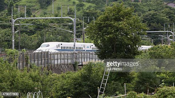 A Nozomi 255 bullet train or 'shinkansen' moves slowly toward Odawara station on June 30 2015 after an apparent suicide attempt on board A man set...