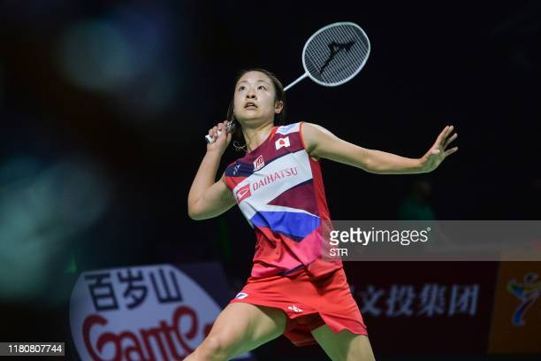 Nozomi Okuhara of Japan hits a return against He Bingjiao of China during their women's singles quarterfinal match at the Fuzhou China Open badminton...