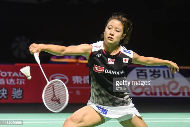 Nozomi Okuhara of Japan hits a return against Tai Tzuying of Taiwan during their women's singles semifinal match at the Fuzhou China Open badminton...