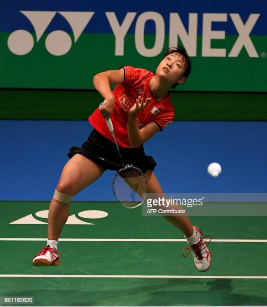Nozomi Okuhara of Japan hits a return towards Zhang Beiwen of the US during their women's singles quarterfinal match at the Japan Open Badminton...