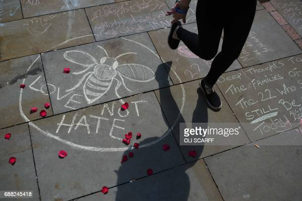 A nperson walks past a chalk message reading 'Love not Hate' in St Ann's Square in Manchester northwest England on May 25 placed in tribute to the...