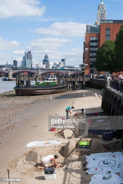 Nr Oxo Tower, London, England, 3/9/10. Artists creating sand sculptures on the sand banks of the River Thames at low tide. View from the South Bank...