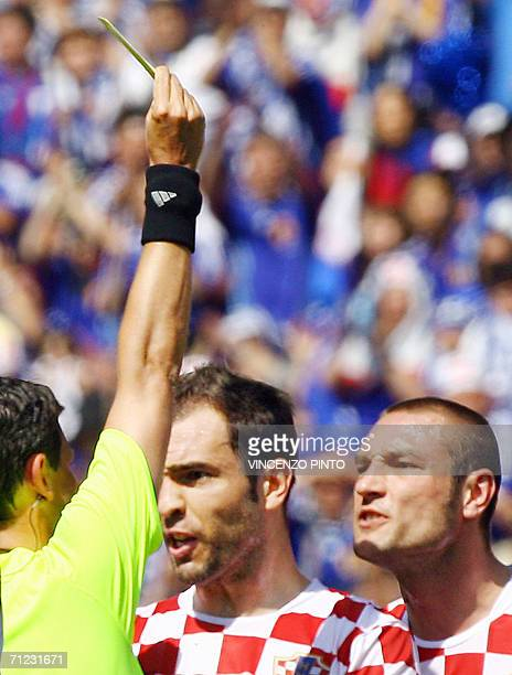 Belgian referee Frank De Bleeckere gives a yellow card to Croatian defender Robert Kovac as Croatian defender Igor Tudor reacts during the World Cup...