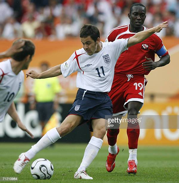 English midfielder Joe Cole kicks the ball as English forward Michael Owen and Trinidad and Tobago's forward Dwight Yorke look on in their opening...