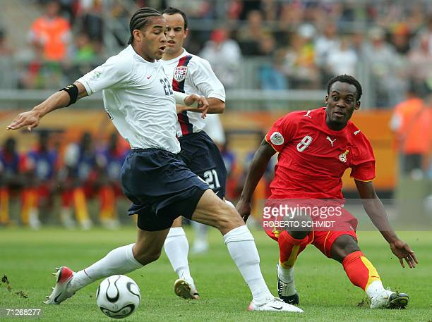 Defender Oguchi Onyewu tries to control the ball as US midfielder Landon Donovan and Ghanaian midfielder Michael Essien look on during the opening...