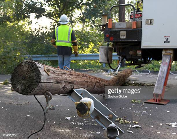 NStar crew Bob Kelland with a downed pole after Hurricane Irene off Cambridge Street in Burlington