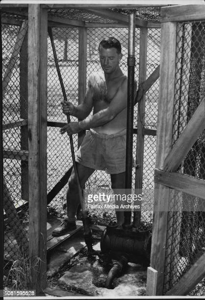 Nth Sydney casis Les Sprouster working the hand pump on the old well in St Leonards part at Nth Sydney December 2 1957