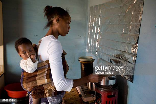 Ntsiuoa Ralefif cooks sorghum porridge with her eight month old baby girl Nthatisi on her back at her home in Harom Hapi Ntsiuoa found out that she...