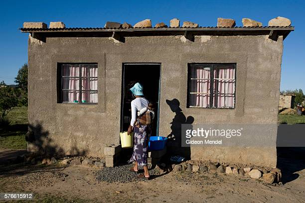 Ntsiuoa Ralefifi with her eight month old HIV negative baby girl Nthatisi carries some water into her home in Harom Hapi Ntsiuoa found out that she...
