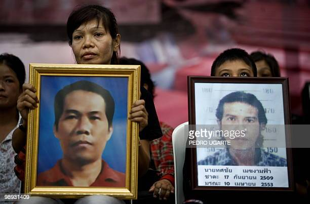 Nuan Chaiman holds a portrait of her husband Jaroon Chaiman next to a boy holding a portrait of Thosachai Mikgramfa both of whom died during clashes...