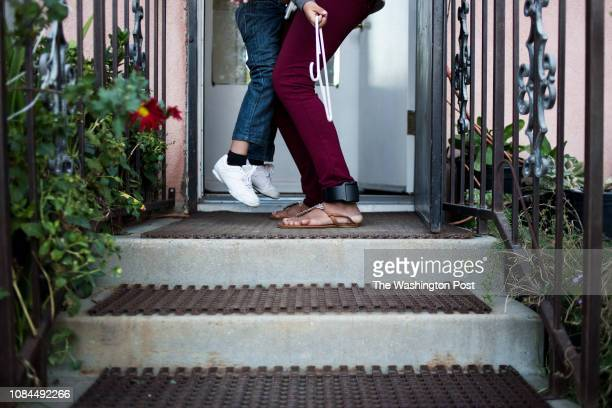 Nubia Estrada Umanzor puts down her son Erickson Estrada while wearing an ankle monitor outside a family member's home in Bakersfield CA on Monday...