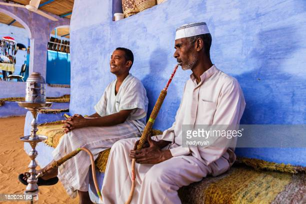 nubian men smoking waterpipe in southern egypt - egypt stock pictures, royalty-free photos & images