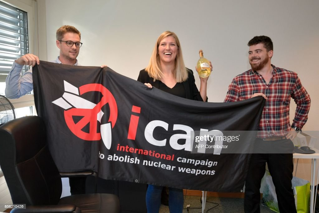 Nuclear disarmament group ICAN coordinator Daniel Hogsta, executive director Beatrice Fihn and her husband Will Fihn Ramsay pose with a banner bearing the group's logo after ICAN won the Nobel Peace Prize for its decade-long campaign to rid the world of the atomic bomb as nuclear-fuelled crises swirl over North Korea and Iran, on October 6, 2017 in Geneva. With the nuclear threat at its most acute in decades, the International Campaign to Abolish Nuclear Weapons, which on October 6 won the Nobel Peace Prize, is urgently pressing to consign the bomb to history. / AFP PHOTO / Fabrice COFFRINI