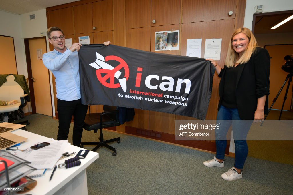 Nuclear disarmament group ICAN executive director Beatrice Fihn (R) and coordinator Daniel Hogsta hold a banner with their logo after ICAN won the Nobel Peace Prize for its decade-long campaign to rid the world of the atomic bomb as nuclear-fuelled crises swirl over North Korea and Iran, on October 6, 2017 in Geneva. With the nuclear threat at its most acute in decades, the International Campaign to Abolish Nuclear Weapons, which on October 6 won the Nobel Peace Prize, is urgently pressing to consign the bomb to history. / AFP PHOTO / Fabrice COFFRINI