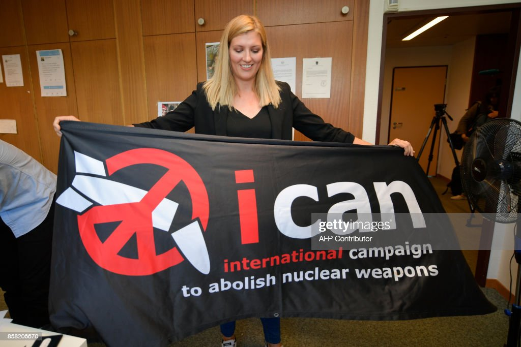 Nuclear disarmament group ICAN executive director Beatrice Fihn holds a banner with their logo after ICAN won the Nobel Peace Prize for its decade-long campaign to rid the world of the atomic bomb as nuclear-fuelled crises swirl over North Korea and Iran, on October 6, 2017 in Geneva. With the nuclear threat at its most acute in decades, the International Campaign to Abolish Nuclear Weapons, which on October 6 won the Nobel Peace Prize, is urgently pressing to consign the bomb to history. / AFP PHOTO / Fabrice COFFRINI