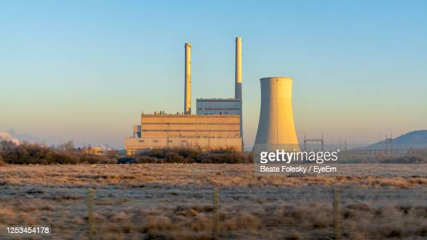 nuclear reactor at industry against clear blue sky at sunset - cooling tower stock pictures, royalty-free photos & images