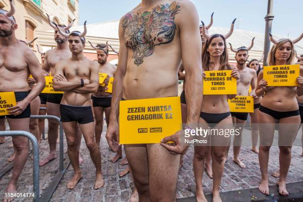 Nude activists against animal cruelty hold banners anti bullfightings during a protesting performance before the San Fermin celebrations in the main...