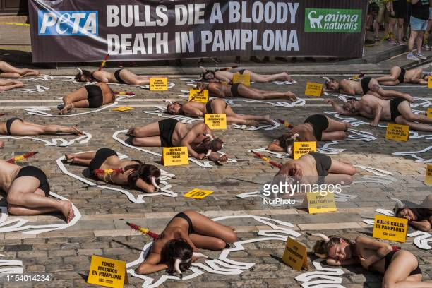 Nude activists against animal cruelty in bullfightings lie on the ground like dead bodies inside chalk outlines of bulls during a protest performance...