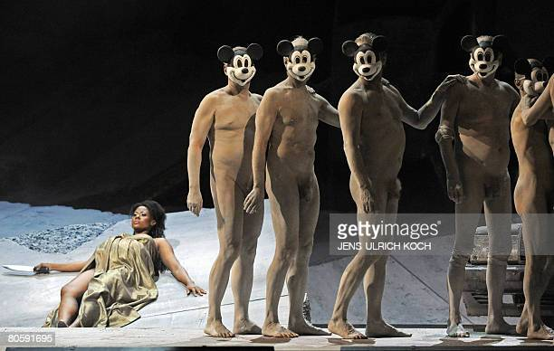 Nude actors wearing Mickeymouse masks walk past opera singer Adina Aaron as Amelia as they perform on stage during a rehearsal of Giuseppe Verdi's...