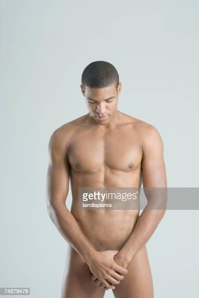 nude african man with hands over groin - ragazzi fighi nudi foto e immagini stock