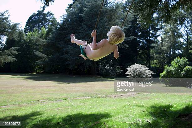 Nude boy playing on swing outdoors