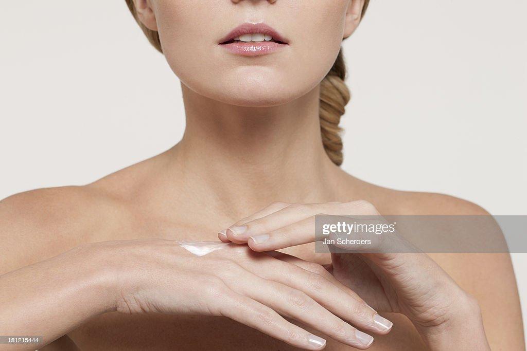 Nude Caucasian woman applying moisturizer : Stock Photo