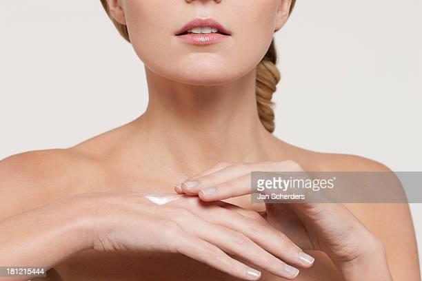 Nude Caucasian woman applying moisturizer