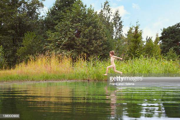 Nude child jumping into lake from pier