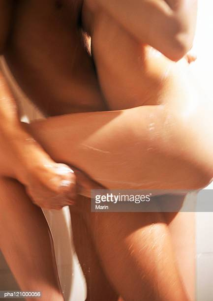 Nude couple embracing in shower, mid-section, side view
