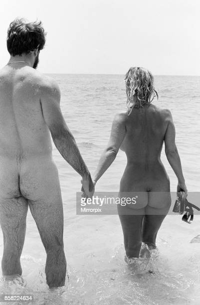 Nude couple enjoy a day out at the beach in the hot summer weather 3rd September 1980