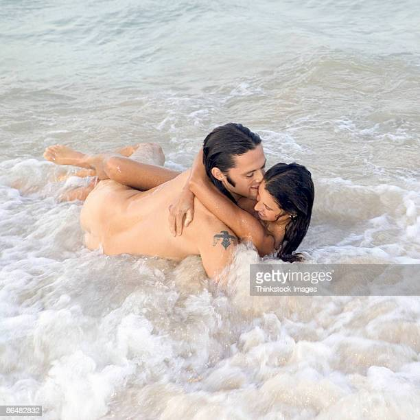 nude couple in ocean - nakenbad bildbanksfoton och bilder