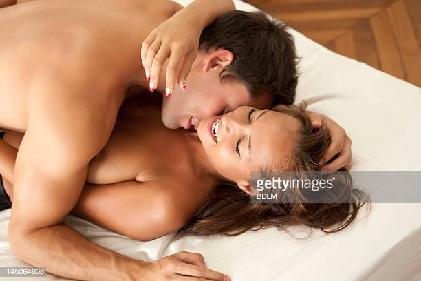 Nude couple kissing in bed