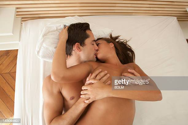 nude couple kissing in bed - seio - fotografias e filmes do acervo