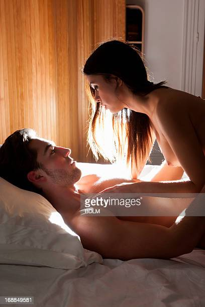 Nude couple laying in bed