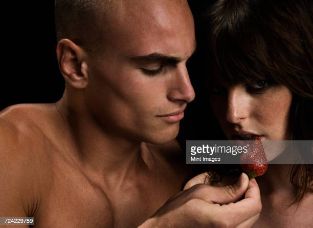 Nude couple, man feeding woman with strawberry.