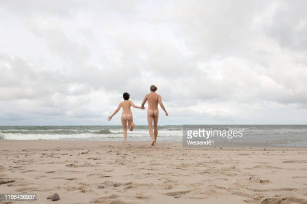 nude couple running to the sea, holding hands - naturists stock pictures, royalty-free photos & images