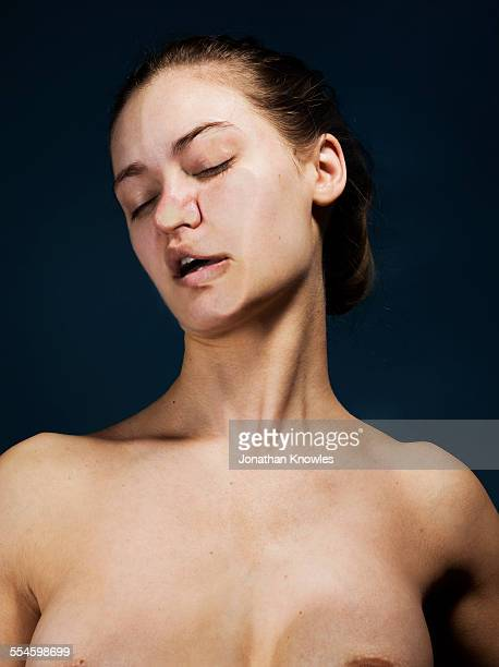 Nude female, face pressed against glass