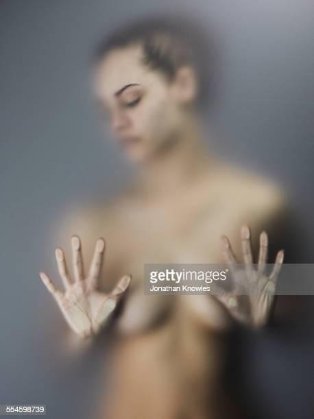 nude female, hands pressed against frosted glass - mani su seno foto e immagini stock