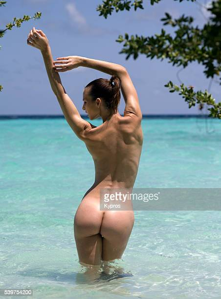 Nude Female Model On A Tropical Beach With Arms Raised, Rear View, Standing In Ocean