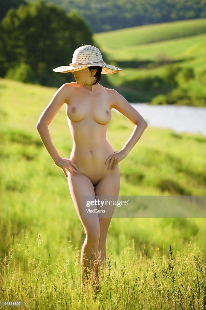 nude Garota no chapéu de palha na grama : Foto de stock