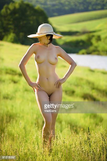 nude girl in hat on grass - dressed undressed women stockfoto's en -beelden