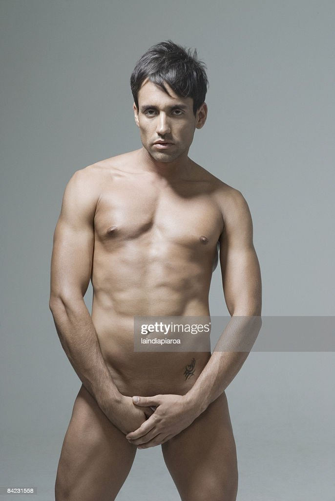 Nude Hispanic man covering his groin : Stock Photo