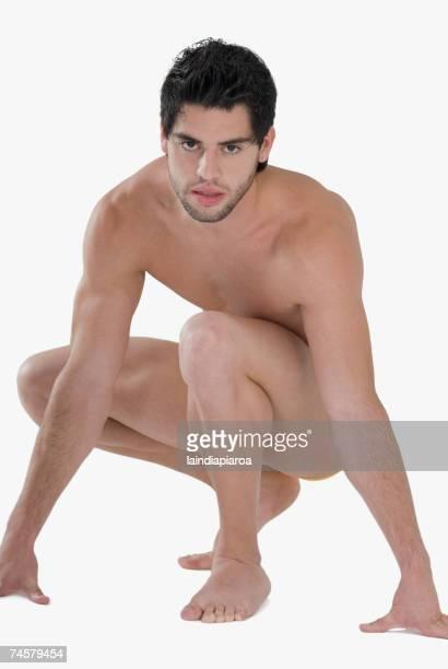 nude hispanic man crouching - hombres desnudos fotografías e imágenes de stock