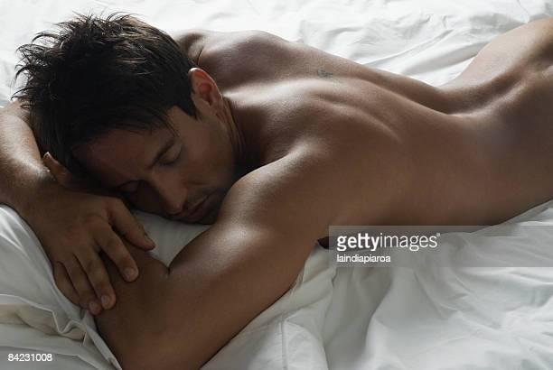 nude hispanic man laying in bed - nuda foto e immagini stock