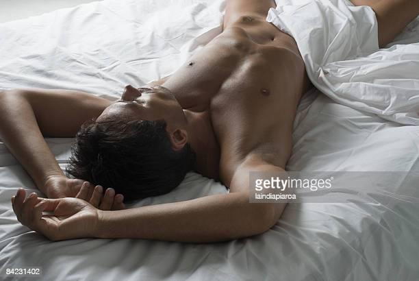 Nude Hispanic man laying in bed