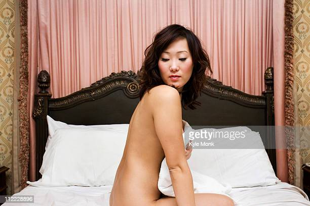 Nude Korean woman kneeling in bed