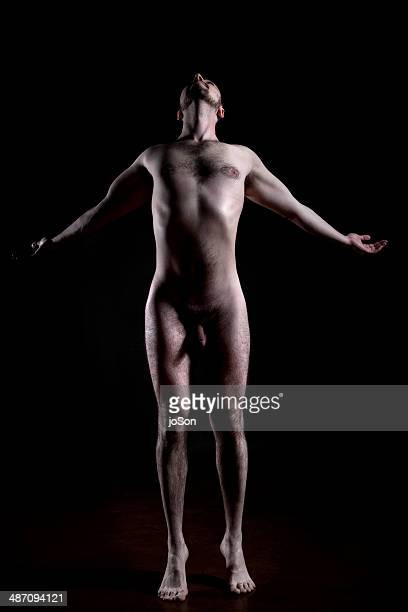 Nude male doing a yoga stretch, looking up